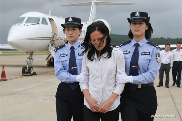 Kuang Wanfang (C), an economic crime suspect, is escorted at the Changle Airport in Fuzhou, Southeast China's Fujian Province, Sept 24, 2015. The woman, who fled to the US in 2001, is suspected of taking part in corruption and bribery, and was repatriated to China thanks to close cooperation between Chinese authorities and their US counterparts. [Photo/Xinhua]